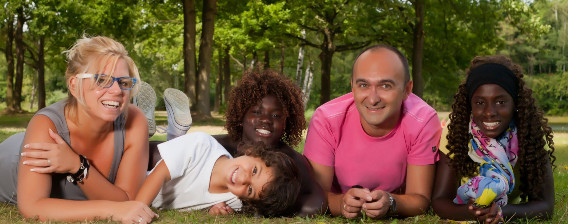 family smiling in the park