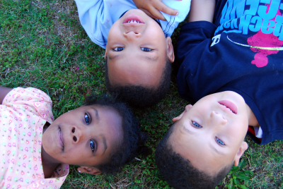 three beautiful children laying on their backs in the grass